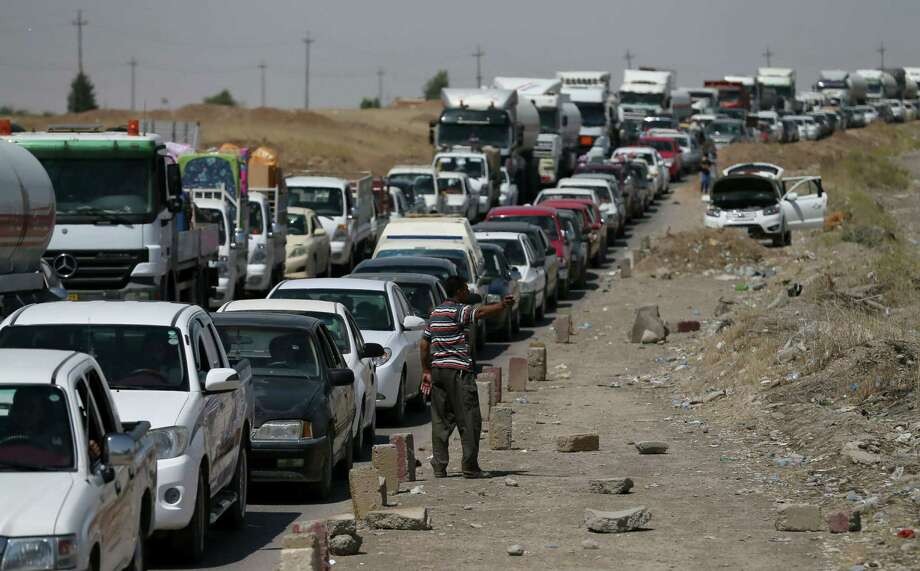 Iraqi families arrive at a checkpoint in the town of al-Muafakiya, 80 kms west of Arbil, on June 14, 2014, after fleeing their homes. Shiite Iran offered to consider working with longtime foe the United States if it takes the lead in helping push back Sunni Arab militants, who have seized a swathe of northern Iraq. AFP PHOTO/KARIM SAHIBKARIM SAHIB/AFP/Getty Images Photo: KARIM SAHIB / AFP