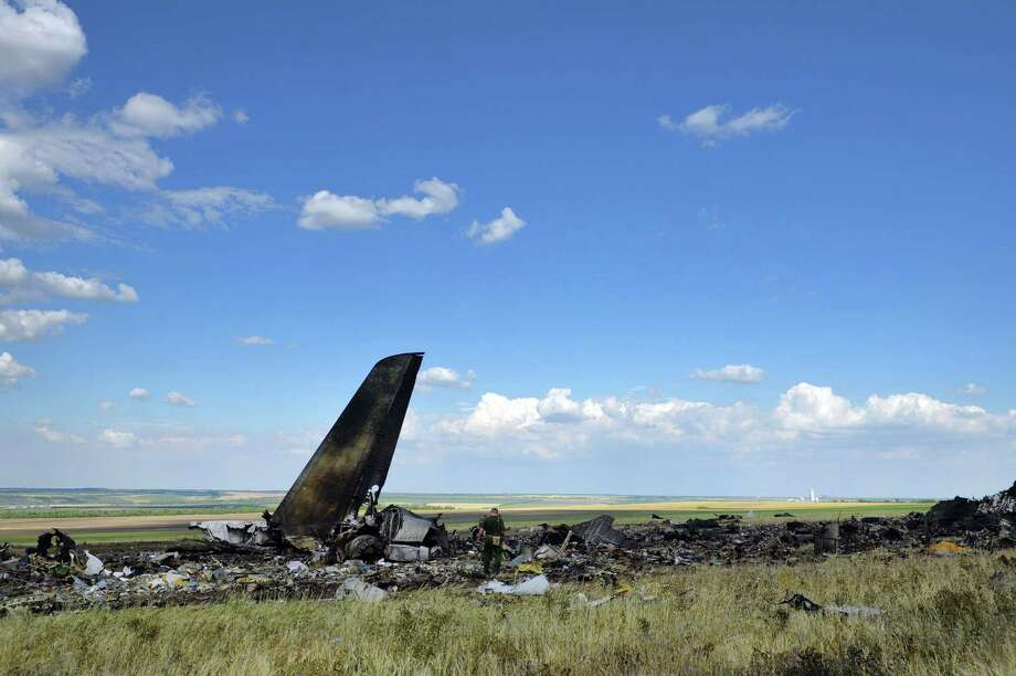 """Pro-Russian separatists look through the debris of an IL-76 transporter which was taken down by pro-Russian rebels early on June 14, on the outskirts of Lugansk June 14, 2014. Ukraine's new Western-backed President Petro Poroshenko vowed Saturday to deliver an """"adequate response"""" to pro-Russian rebels who downed a military transport plane, killing 49 troops. AFP PHOTO / DANIEL MIHAILESCUDANIEL MIHAILESCU/AFP/Getty Images ORG XMIT: - Photo: DANIEL MIHAILESCU / AFP"""