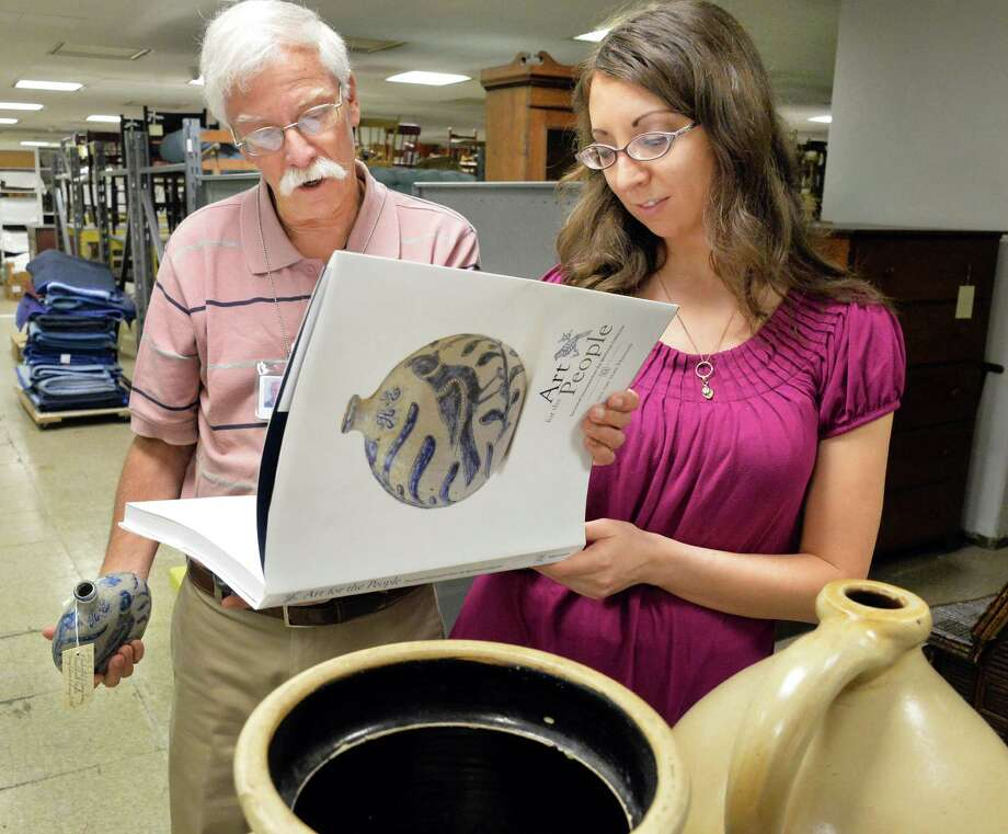 "Historian emeritus John Scherer, left, and museum staffer Antonia Valentine look through the museum publication, ""Art for the People"" of the Weitsman Stoneware Collection, donated by scrap metal mogul Adam Weitsman at the NYS Museum Thursday June 5, 2014, in Albany, NY.  (John Carl D'Annibale / Times Union) Photo: John Carl D'Annibale / 00027193A"