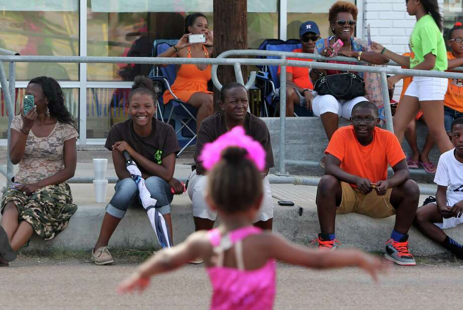 Spectators smile as they watch Design To Dance team perform during the Emancipation Park's Juneteenth Parade in Houston. Photo: Mayra Beltran, Houston Chronicle / © 2014 Houston Chronicle