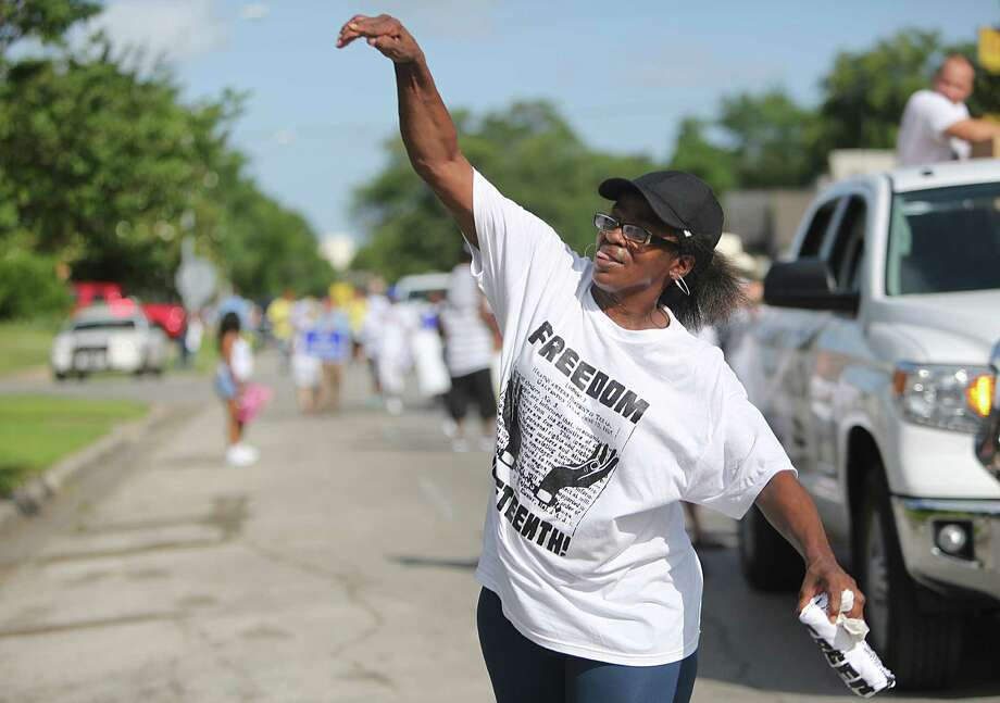 Melanie Hughes tosses free Juneteenth t-shirts during the Emancipation Park's Juneteenth Parade on Saturday in Houston. Photo: Mayra Beltran, Houston Chronicle / © 2014 Houston Chronicle