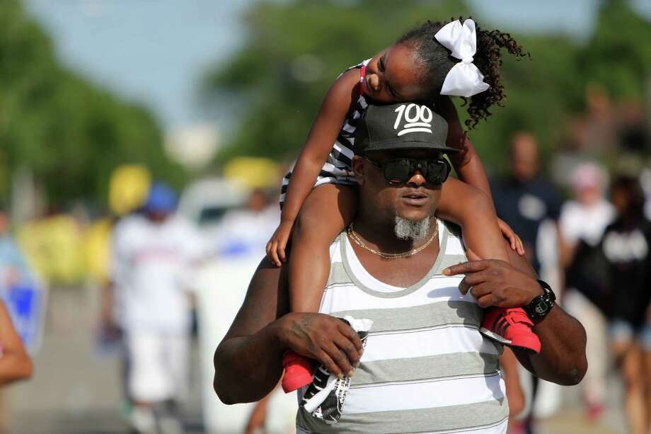 Brandon Nelson carries daughter Brooklyn Jackson, 3, on his shoulders along Wheeler St. during the Emancipation Park's Juneteenth Parade gets underway along Wheeler St. on Saturday in Houston. Photo: Mayra Beltran, Houston Chronicle / © 2014 Houston Chronicle