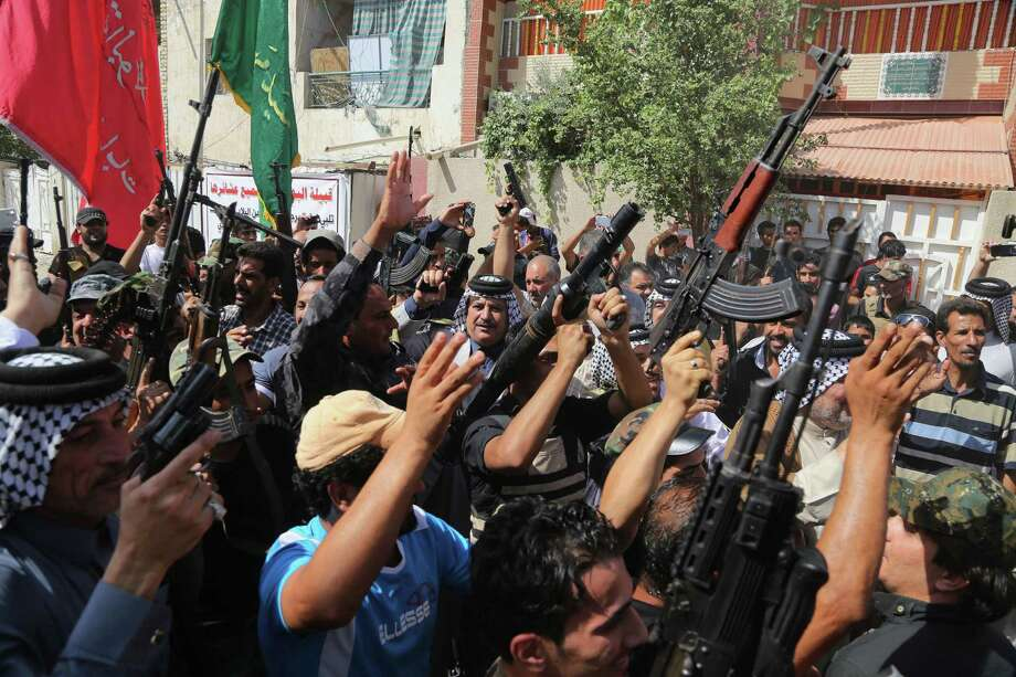 Iraqi Shiite tribal fighters raise their weapons and chant slogans against the al-Qaida inspired Islamic State of Iraq and the Levant (ISIL) in Baghdad's Sadr city, Iraq, Saturday, June 14, 2014. Thousands of Shiites from Baghdad and across southern Iraq answered an urgent call to arms Saturday, joining security forces to fight the Islamic militants who have captured large swaths of territory north of the capital and now imperil a city with a much-revered religious shrine. (AP Photo/Karim Kadim) Photo: Karim Kadim, STF / AP