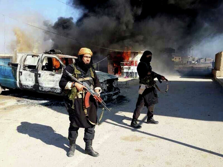 FILE - This undated file image posted on a militant website on Jan. 4, 2014, which is consistent with other AP reporting, shows Shakir Waheib, a senior member of the al-Qaida breakaway group Islamic State of Iraq and the Levant (ISIL), left, next to a burning police vehicle in Iraq's Anbar Province. For the al-Qaida breakaway group that overran parts of Iraq this week, the border between that country and Syria, where it is also fighting, may as well not even be there. The group, wants to establish a Shariah-ruled mini-state bridging both countries, in effect uniting a Sunni heartland across the center of the Mideast. (AP Photo via Militant Website, File) Photo: Uncredited, HOPD / Militant Website