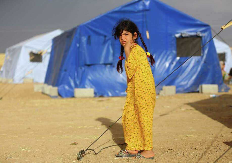 Refugees flee MosulAn Iraqi girl from Mosul stands outside her family's tent at Khazir refugee camp outside Irbil, 217 miles north of Baghdad, on June 13, 2014. The militants' capture of Mosul and Tikrit makes their dream of a new Islamic state look more realistic. The group already controls a swath of eastern Syria along the Euphrates River. Photo: Uncredited, STR / AP