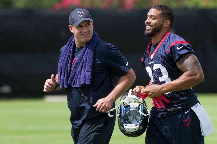 With no Segways to ride, coach Bill O'Brien, left, jogs across the field with running back Arian Foster during the Texans' organized team activities last week. O'Brien also takes time for a little one-on-one conversation with top draft pick Jadeveon Clowney, right. Photo: Brett Coomer, Staff / © 2014 Houston Chronicle