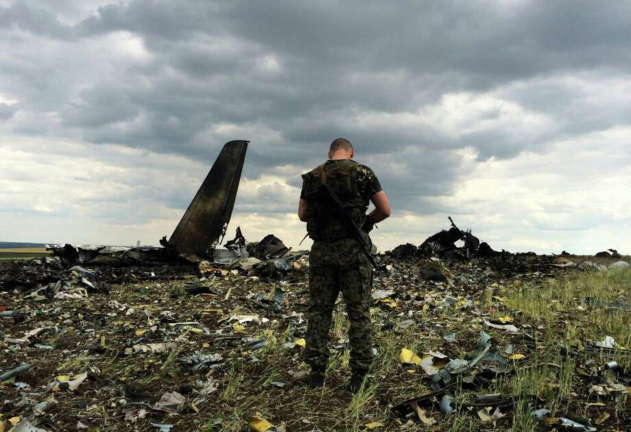 A pro-Russian fighter guards the site of remnants of a downed Ukrainian army aircraft Il-76 at the airport near Luhansk, Ukraine, Saturday, June 14, 2014. Pro-Russian separatists shot down the military transport plane Saturday in the country's restive east, killing all 49 service personnel on board, Ukrainian officials said. (AP Photo/Evgeniy Maloletka) Photo: Evgeniy Maloletka, STR / AP