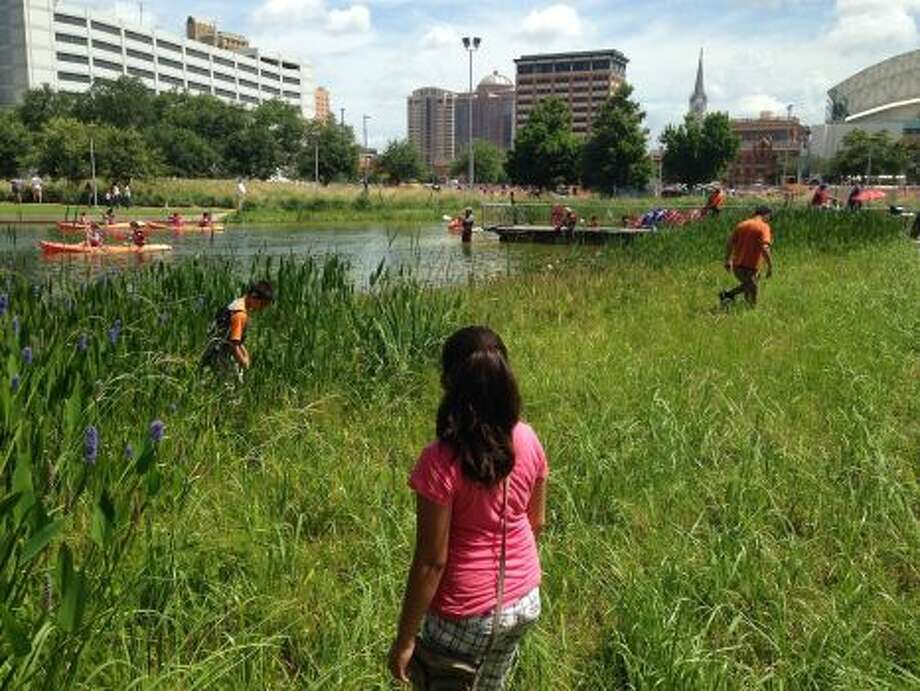 In hopes of finding $1,500 in hidden cash, visitors search through brush and weeds at Discovery Green park on Saturday. The hunt was sparked by social media posts from Twitter account @HiddenCash, which announced the search.