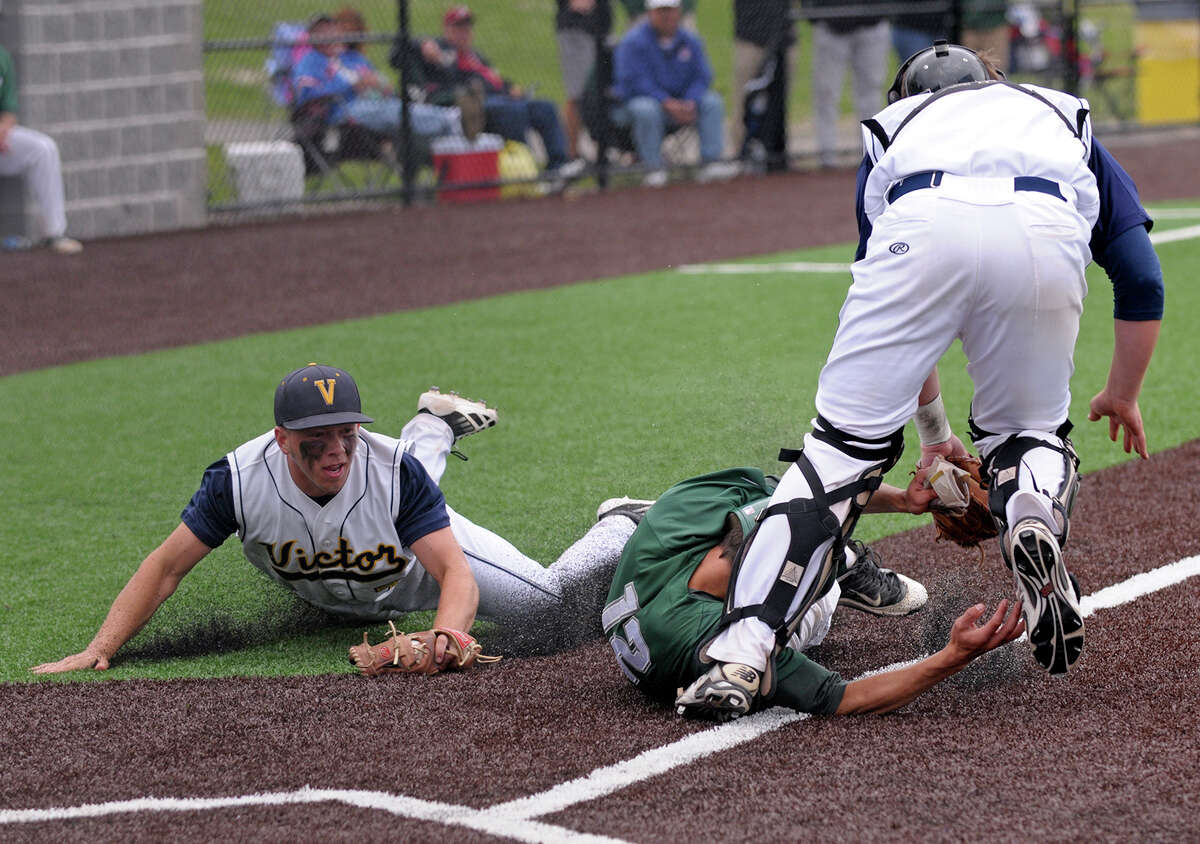 Shenendehowa Plainsmen outfielder Kyle McAlonie #12, center, is tagged by Victor catcher Brett Prong, right, out after a rundown in the bottom of the 1st inning during the NYSPHSAA AA championship game on Saturday, June 14, 2014 at Gary Crooks Field in Endwell, N.Y. (Tom Brenner/ special to the Times Union) ORG XMIT: 00027326A
