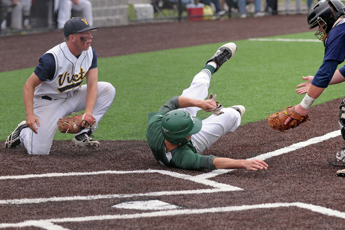 Shenendehowa Plainsmen outfielder Kyle McAlonie, center, is tagged out by Victor catcher Brett Prong, right, after a rundown in the bottom of the 1st inning during the NYSPHSAA AA championship game versus Victor Blue Devils on Saturday, June 14, 2014 at Gary Crooks Field in Endwell, N.Y. (Tom Brenner/ special to the Times Union)