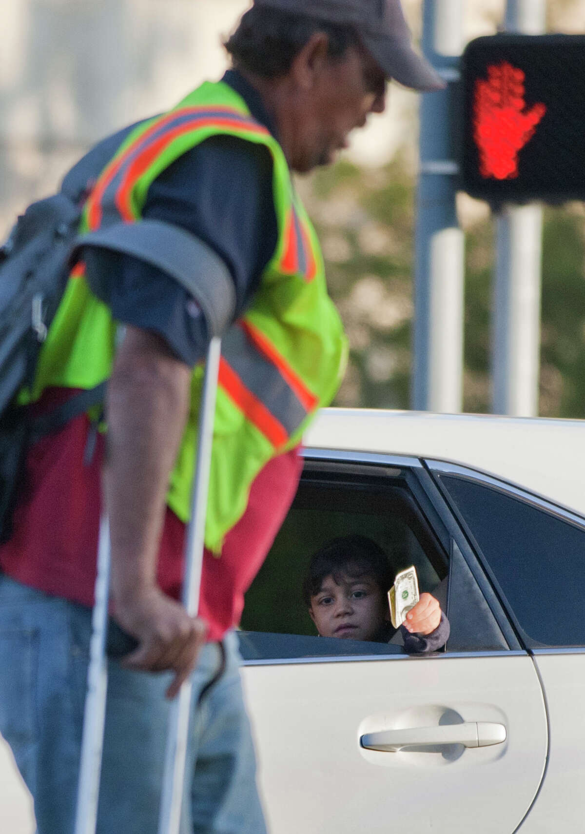 Heading for his regular panhandling spot and not yet paying attention, Carbonneau misses out on a few dollars from a passing car on Woodway at the Loop.