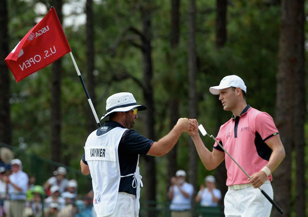Martin Kaymer, right, gives caddie Craig Connelly a fist bump after the U.S. Open leader carded an eagle on the fifth hole Saturday.