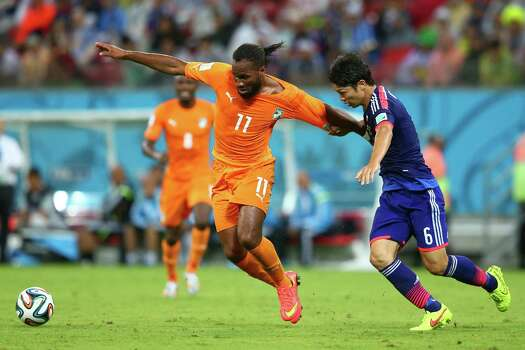 RECIFE, BRAZIL - JUNE 14: Didier Drogba of the Ivory Coast holds off a challenge by Masato Morishige of Japan during the 2014 FIFA World Cup Brazil Group C match  between the Ivory Coast and Japan at Arena Pernambuco on June 14, 2014 in Recife, Brazil. Photo: Julian Finney, Getty Images / 2014 Getty Images