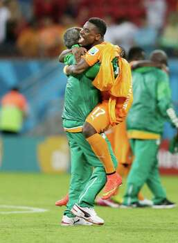 Ivory Coast's Serge Aurier is hugged by a team member after their 2-1 victory over Japan in a group C World Cup soccer match at the Arena Pernambuco in Recife, Brazil, Sunday, June 15, 2014.  (AP Photo/Dolores Ochoa) Photo: Dolores Ochoa, Associated Press / AP