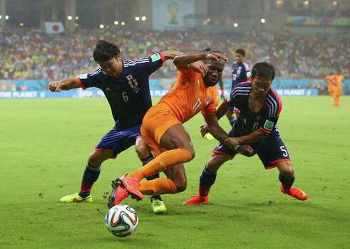 RECIFE, BRAZIL - JUNE 14:  Masato Morishige (L) and Yuto Nagatomo of Japan challenge Didier Drogba of the Ivory Coast during the 2014 FIFA World Cup Brazil Group C match  between the Ivory Coast and Japan at Arena Pernambuco on June 14, 2014 in Recife, Brazil.  (Photo by Julian Finney/Getty Images) *** BESTPIX *** Photo: Julian Finney, Getty Images / 2014 Getty Images