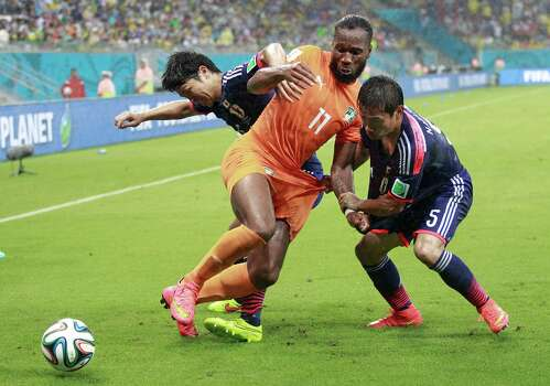 Japan's Masato Morishige, left, and Yuto Nagatomo (5) struggle with Ivory Coast's Didier Drogba (11) during the group C World Cup soccer match at the Arena Pernambuco in Recife, Brazil, Saturday, June 14, 2014.  (AP Photo/Dolores Ochoa) Photo: Dolores Ochoa, Associated Press / AP