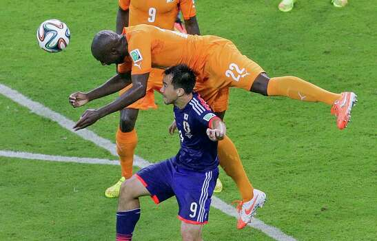 Japan's Shinji Okazaki, bottom, and Ivory Coast's Sol Bamba challenge for the ball during the group C World Cup soccer match between Ivory Coast and Japan at the Arena Pernambuco in Recife, Brazil, Saturday, June 14, 2014. (AP Photo/Hassan Ammar) Photo: Hassan Ammar, Associated Press / AP