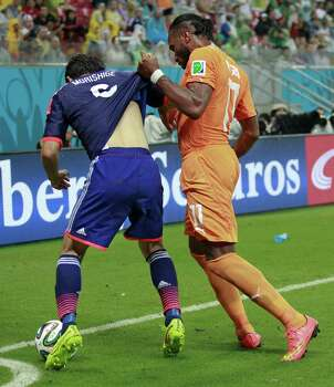 Ivory Coast's Didier Drogba, right, holds on to the shirt of Japan's Masato Morishige, left, during the group C World Cup soccer match at the Arena Pernambuco in Recife, Brazil, Saturday, June 14, 2014.  (AP Photo/Dolores Ochoa) Photo: Dolores Ochoa, Associated Press / AP