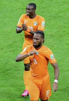 Ivory Coast's Didier Drogba , front, and Constant Djakpa leave the pitch after winning the group C World Cup soccer match between Ivory Coast and Japan at the Arena Pernambuco in Recife, Brazil, Saturday, June 14, 2014. Ivory Coast won 2-1. (AP Photo/Hassan Ammar) Photo: Hassan Ammar, Associated Press / AP