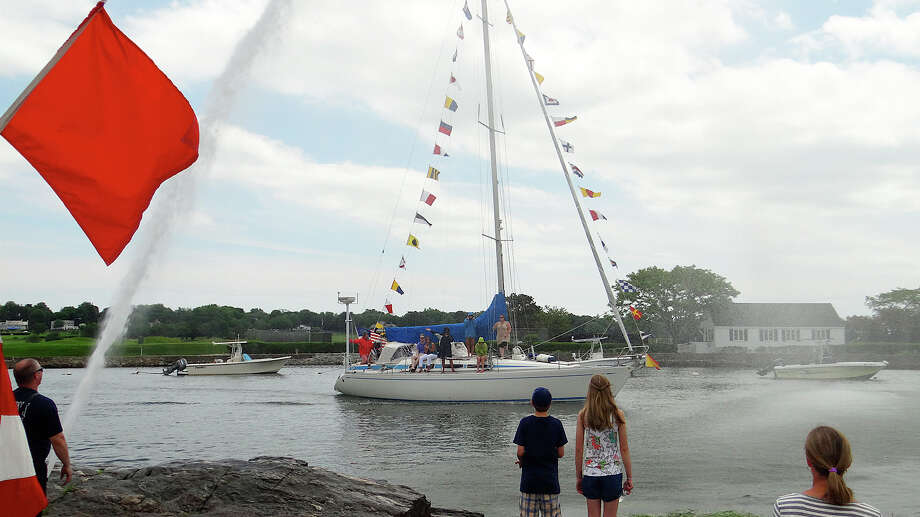 "The sailboat ""Merlin,"" festooned in flags, passes under a plume of water as it proceeds out to sea from Southport Harbor during Saturday's Pleassing of the Fleet ceremony. Photo: Mike Lauterborn / Fairfield Citizen"