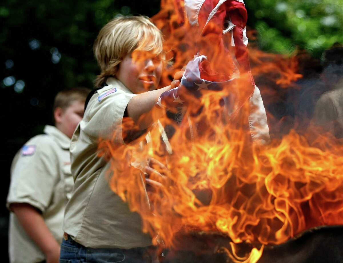 Roseburg, Ore. Boy Scout Troop 46 member Kadin Gilliam tosses a weathered flag into an awaiting fire during a flag disposal ceremony in Dillard, Ore. June 14.