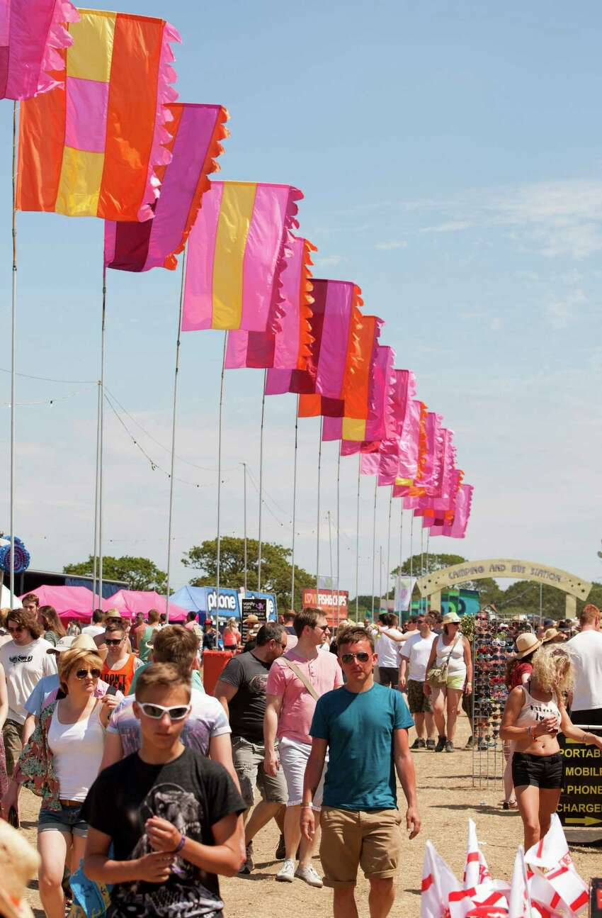 Festival goers arrive at Isle of Wight Festival in Newport on the Isle of Wight on Friday, June 13, 2014. Thousands of people are to attend the three day event with headliners, Biffy Clyro, Calvin Harris, Red Hot Chilli Peppers and Kings of Leon.
