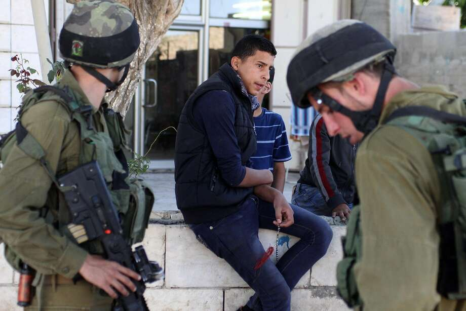 Israeli infantry soldiers prepare to search for teenage captives in the West Bank village of Beit Einun. Photo: Quique Kierszenbaum, McClatchy-Tribune News Service