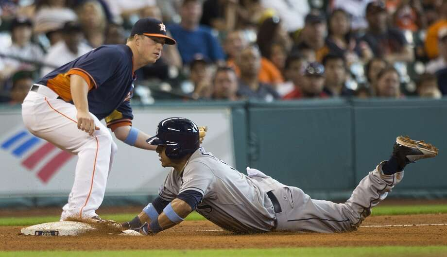 Rays shortstop Yunel Escobar (11) slides into third past the tag of Astros third baseman Matt Dominguez after a single by Rays catcher Jose Molina during the sixth inning. Photo: Brett Coomer, Houston Chronicle