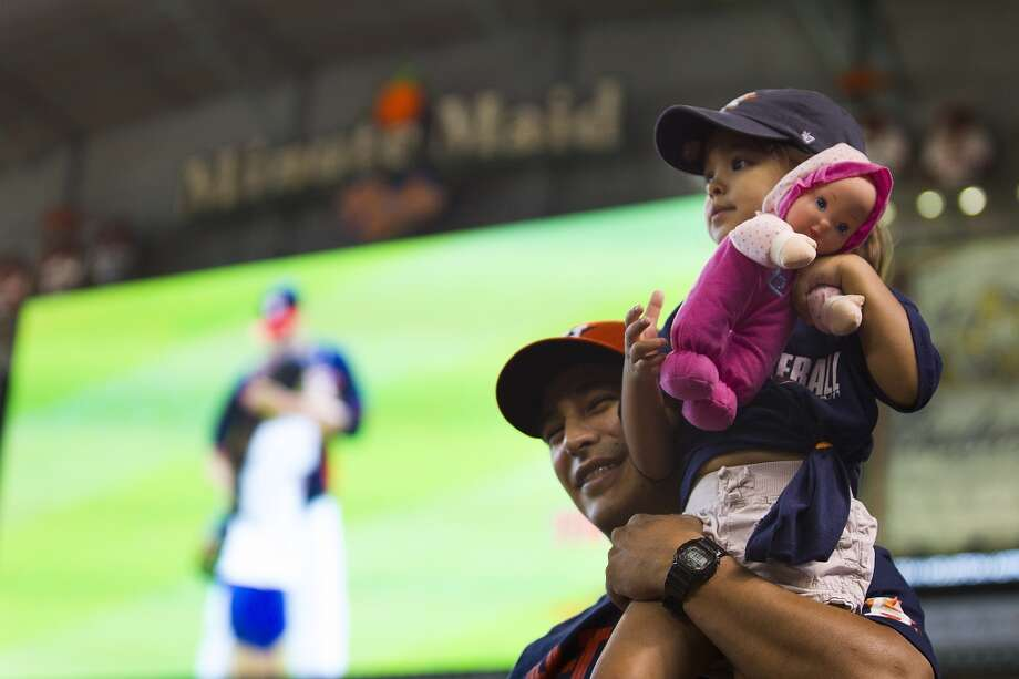 Mike Ceballos holds his daughter, Lilliana, before the game. Photo: Brett Coomer, Houston Chronicle