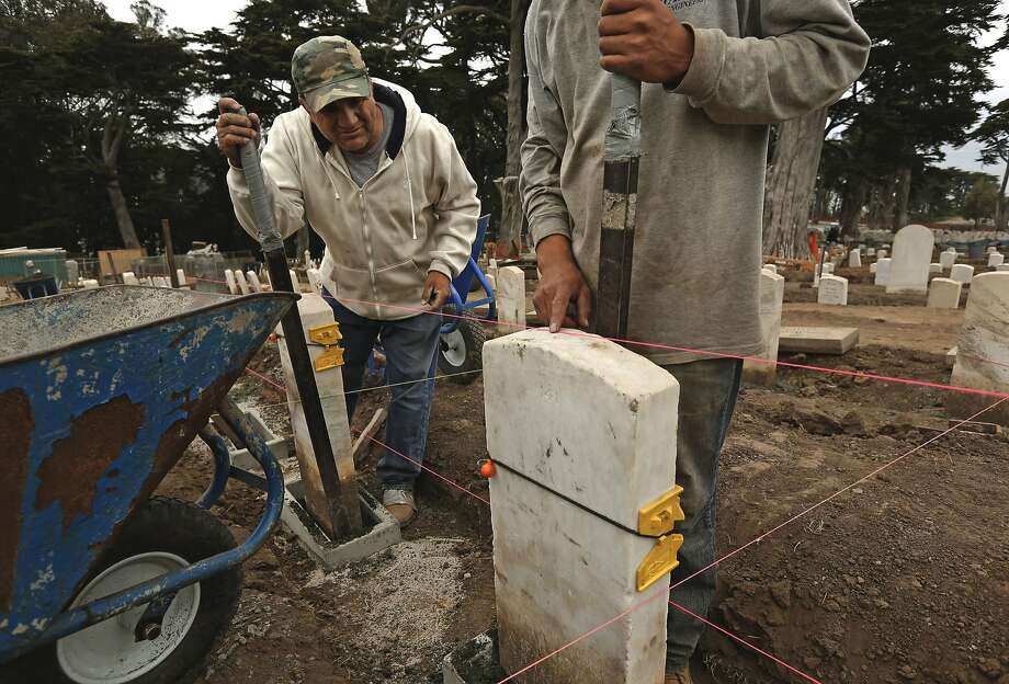 George Navarro (left) and Danny Rodas work at leveling every one of the headstones in the Presidio's historic San Francisco National Cemetery - thousands of them. The graves date back as far as the 1850s. Photo: Michael Macor, The Chronicle