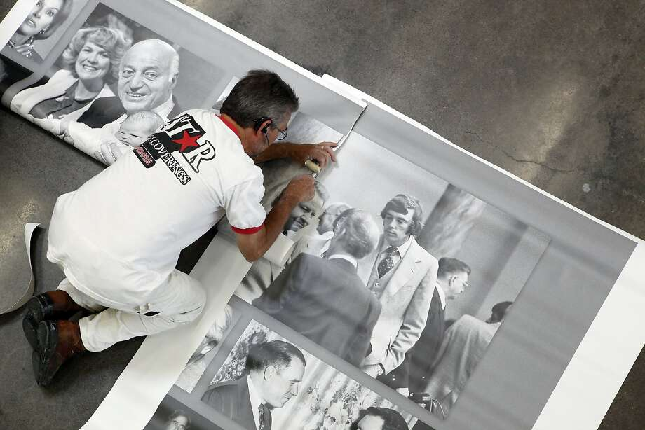 Gary Thomas assembles a collage of past Democratic leaders for the walls of the state party's new offices in Sacramento. Photo: Michael Short, The Chronicle