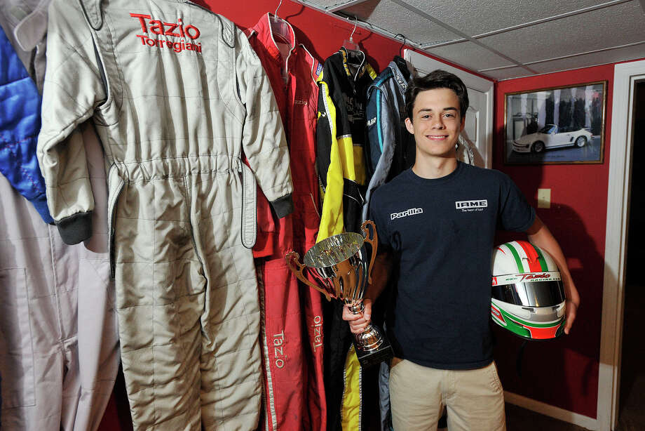 Stamford High School freshman Tazio Torregiani poses for a photograph next to his flame retardant racing suits at his home in Stamford, Conn., on Sunday, June 15, 2014. Torregiani races his go-karts all over the world. He has over 30 first place finishes in his career since he started at the age of six. Photo: Jason Rearick / Stamford Advocate