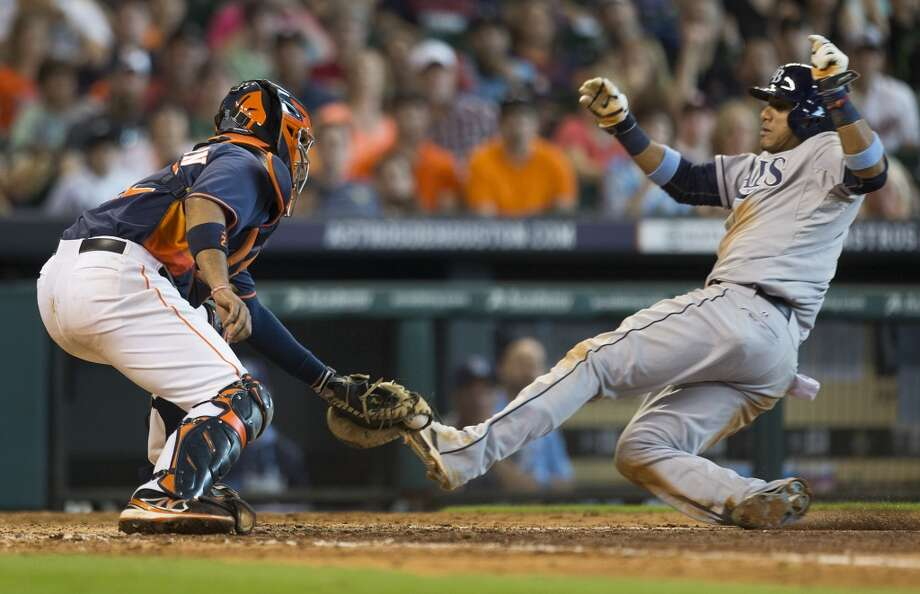 Rays shortstop Yunel Escobar, right, slides into the tag by Astros catcher Carlos Corporan during the eighth inning. Photo: Brett Coomer, Houston Chronicle