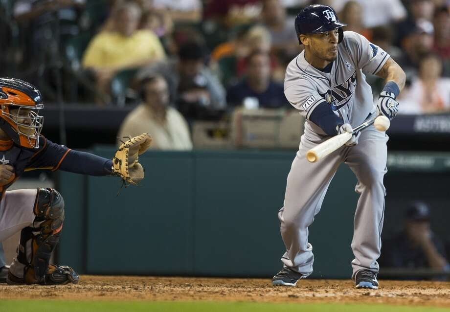 Rays center fielder Desmond Jennings lays down a sacrifice bunt in front of Astros catcher Carlos Corporan, left, during the eighth inning. Photo: Brett Coomer, Houston Chronicle