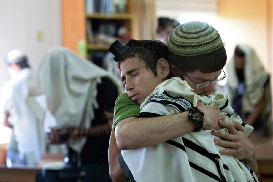 Israeli Jewish religious students on Sunday hug prior to a prayer at the synagogue where two of the missing Israeli teens studied, in the Jewish settlement of Kfar Etzion. Prime Minister Benjamin Netanyahu blamed the militant Palestinian movement Hamas for the teens' kidnapping. Photo: Sebastian Scheiner, STF / AP
