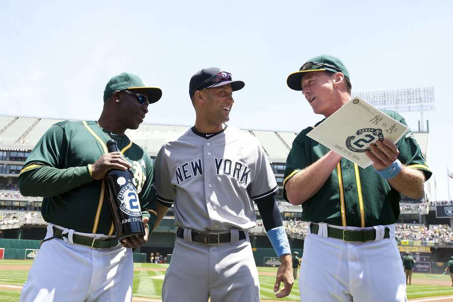 The Yankees' Derek Jeter is presented with gifts by A's coach Chili Davis and manager Bob Melvin. Photo: Jason O. Watson, Getty Images