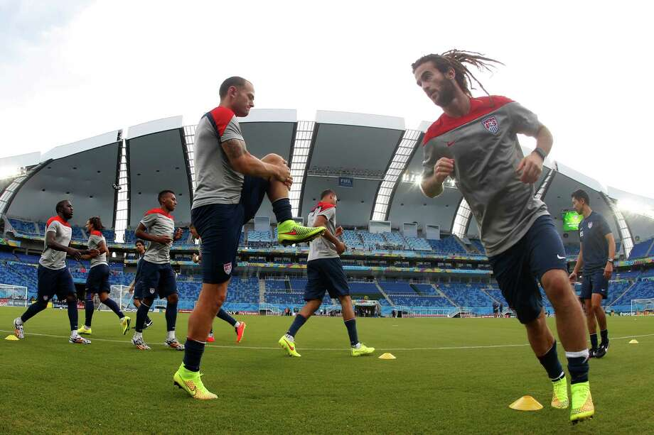 In this photograph taken with a fisheye lens, United States players warm up during an official training session the day before the group G World Cup soccer match between Ghana and the United States at the Arena das Dunas in Natal, Brazil, Sunday, June 15, 2014.  (AP Photo/Julio Cortez) ORG XMIT: BRAJC113 Photo: Julio Cortez / AP