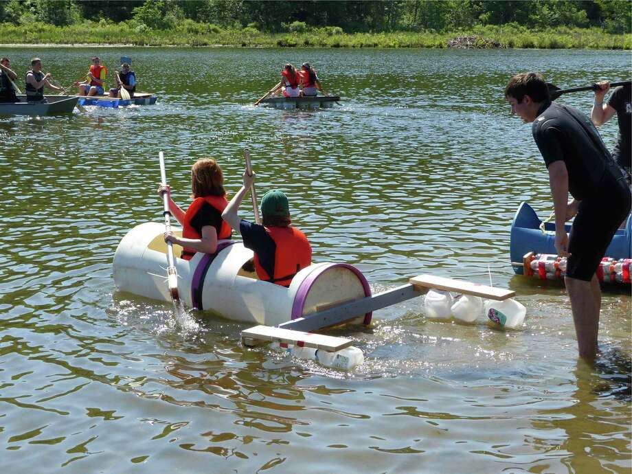 Students enrolled in the Ravena-Coeymans-Selkirk High School design and drawing for production class participated in the annual Recyclable Boat Regatta at Lawson Lake in Coeymans on June 7. The eight boats were designed and constructed entirely of recyclable materials, from rafts secured to plastic buckets, barrels and similar materials, to kayak-type boats made from large plastic drums. (Submitted photo)