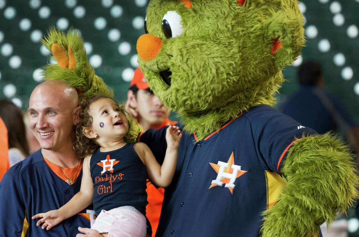 Matt McCurley, left, and his daughter, Madison, pose for a photo with Houston Astros mascot Orbit during the Astros Foundation 2nd Annual Picnic in the Park in the outfield at Minute Maid Park Sunday, June 15, 2014, in Houston.