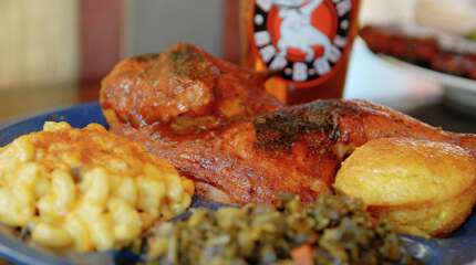 """Beauty shot of the """"All Natural"""", Half BBQ Chicken Plate, from the True Blue Bar-B-Que Pit Plates"""" portion of the menu at the new Dinosaur Bar-B-Que, on River St. in downtown Troy, NY, on Monday, Jan. 10, 2011.  The Chicken is Apple brined, pit smoked and slathered with our original BBQ sauce.  The plates include Honey Hush Cornbread and 2 Homemade Sides, in this case the Mac and Cheese, and the Collard and mustard greens.  The Bar-B-Que new chain location is now at the site of the former Castaway's and other restaurants on River St. along the Hudson River in Troy.  The chain motto is """"Always Good Smoke"""". Photos for Matters of Taste Restaurant review column.     (Luanne M. Ferris / Times Union )"""