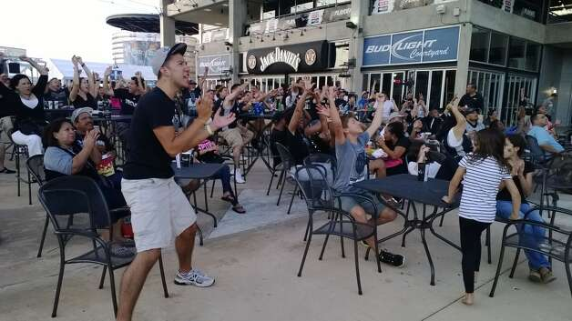 Fans jump from their seats as Manu scores in the second quarter at Bud Light Courtyard on Sunday, June 15, 2014. Photo: Jacob Beltran/San Antonio Express-News