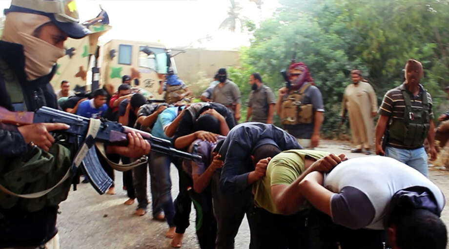 This image posted on a militant website on Saturday appears to show ISIS troops leading away captured Iraqi soldiers after taking over a base in Tikrit, Iraq. Photo: HOEP / AP