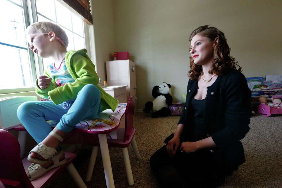 In this April 29, 2014 photo, mother of child with cancer Moriah Barnhart watches her three year old daughter Dahlia at their home in Colorado Springs. Barnhart, frustrated with mainstream medical treatments and facing the possibility of intervention by child protective authorities, moved to Colorado to treat Dahlia using what some describe as cutting edge cannabis medication. Hundreds of parents in similar situations find themselves at the center of a debate about how far government can and should reach when parents push against legal boundaries to save their childrens' lives. (AP Photo/Brennan Linsley) Photo: Brennan Linsley, STF / AP