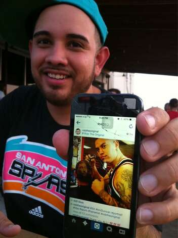 Spurs fan Jesse Almaguer shows a photo of his hair during last year's NBA Finals on his phone during Game 5 on June 15, 2014. Photo: Jennifer R. Lloyd/San Antonio Express-News