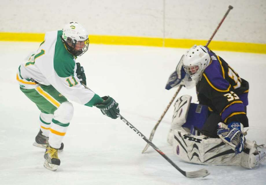 Trinity's CJ DelVaglio, left, slips a goal past Westhill's Wade McManus, right, during an FCIAC boys hockey game at Terry Conners Rink in Stamford, Conn. on Monday, Feb. 15, 2010. Photo: Chris Preovolos / Stamford Advocate