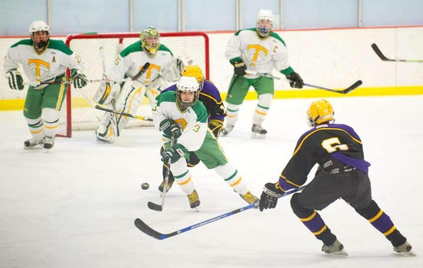 Trinity's Stephen Franze, left, and Westhill's Darnell Dorival, right, during an FCIAC boys hockey game at Terry Conners Rink in Stamford, Conn. on Monday, Feb. 15, 2010.