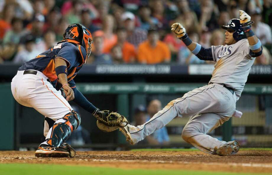 Astros catcher Carlos Corporan is waiting with the tag as Tampa Bay's Yunel Escobar attempts to score in the eighth inning Sunday. Photo: Brett Coomer, Staff / © 2014 Houston Chronicle