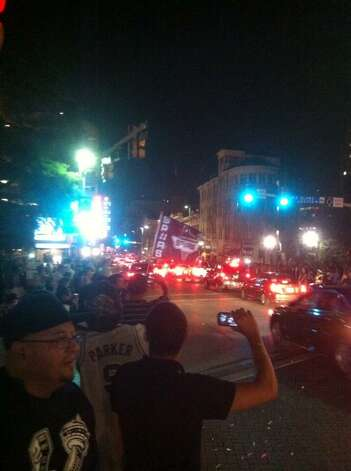 On the corner of Commerce and Lasoya more than a dozen Spurs fans are waving large flags and people climbing on top of cars after the Spurs won their fifth NBA title on Sunday, June 15, 2014. Photo: San Antonio Express-News