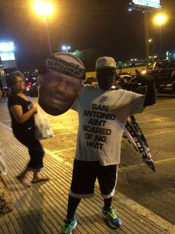 """A Spurs fan shows off his """"San Antonio ain't scared of no Heat"""" shirt as fans take to the street's to celebrate the Spurs' fifth title on Sunday, June 15, 2014. Photo: Mitchell Ferman / San Antonio Express-News"""