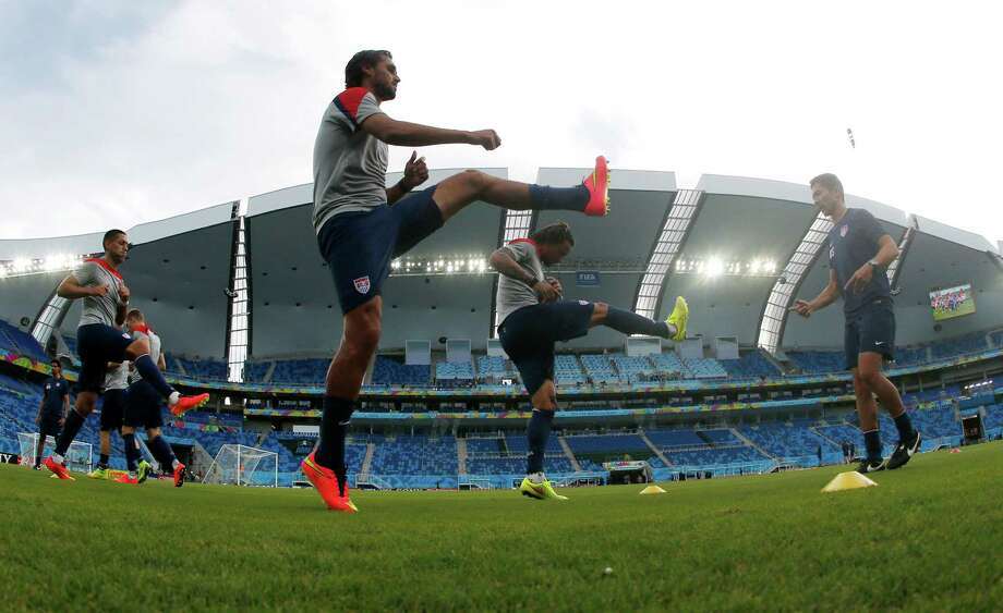 In this photograph taken with a fisheye lens, United States players warm up during an official training session the day before the group G World Cup soccer match between Ghana and the United States at the Arena das Dunas in Natal, Brazil, Sunday, June 15, 2014.  (AP Photo/Julio Cortez) ORG XMIT: BRAJC123 Photo: Julio Cortez / AP